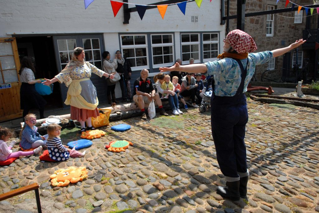 Marie Louise Cochrane, aka Mrs. Mash (wearing skirt and apron) and Jan Bee Brown (wearing overalls) of The Thrive Archive performing at the open day of the Scottish Fisheries Museum in Anstruther, Fife on June 4, 2016.